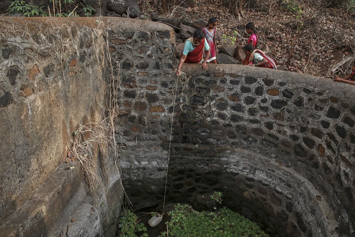 Bhaagi, third wife of Sakharam Bhagat takes out water from a well as Sakhri helps her outside their village in Denganmal.
