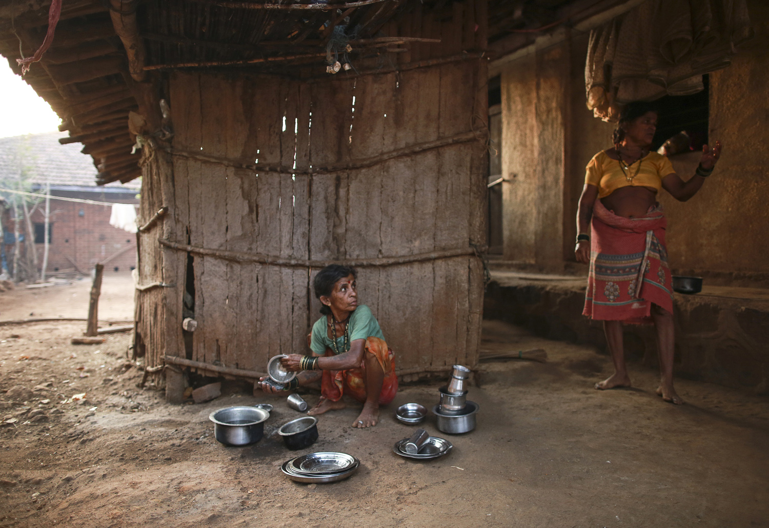 Sakhri (L), the second wife of Sakharam Bhagat, listens to Tuki, the first wife of Sakharam Bhagat as she washes utensils outside their house in Denganmal village.