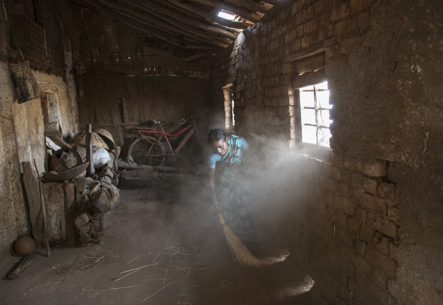 Shivarti, second wife of Namdeo, cleans a room inside their house in Denganmal village.