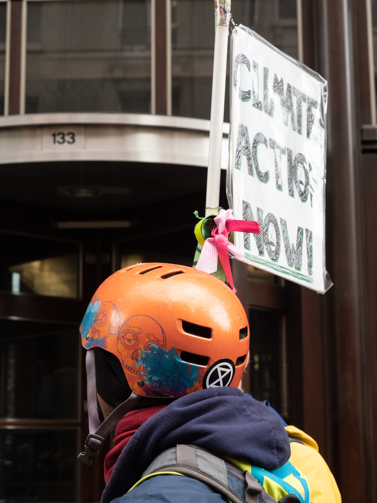 A protestor with the Extinction Rebellion logo on his helmet outside the offices of Goldman Sachs International at 133 Fleet St.
