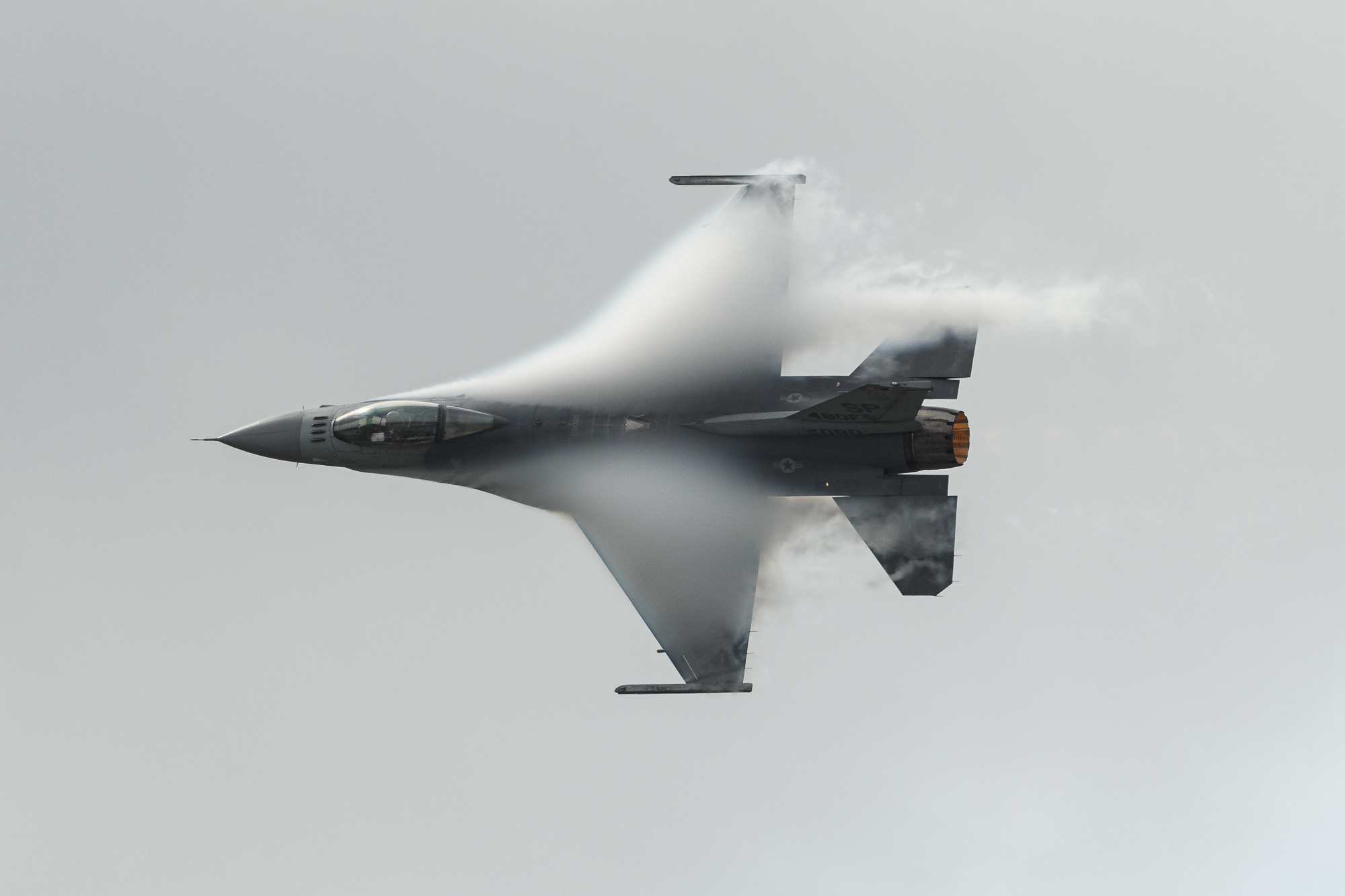 USAF F-16, afterburner on, creating its own clouds as it pulls a high-G turn under the low cloudbase