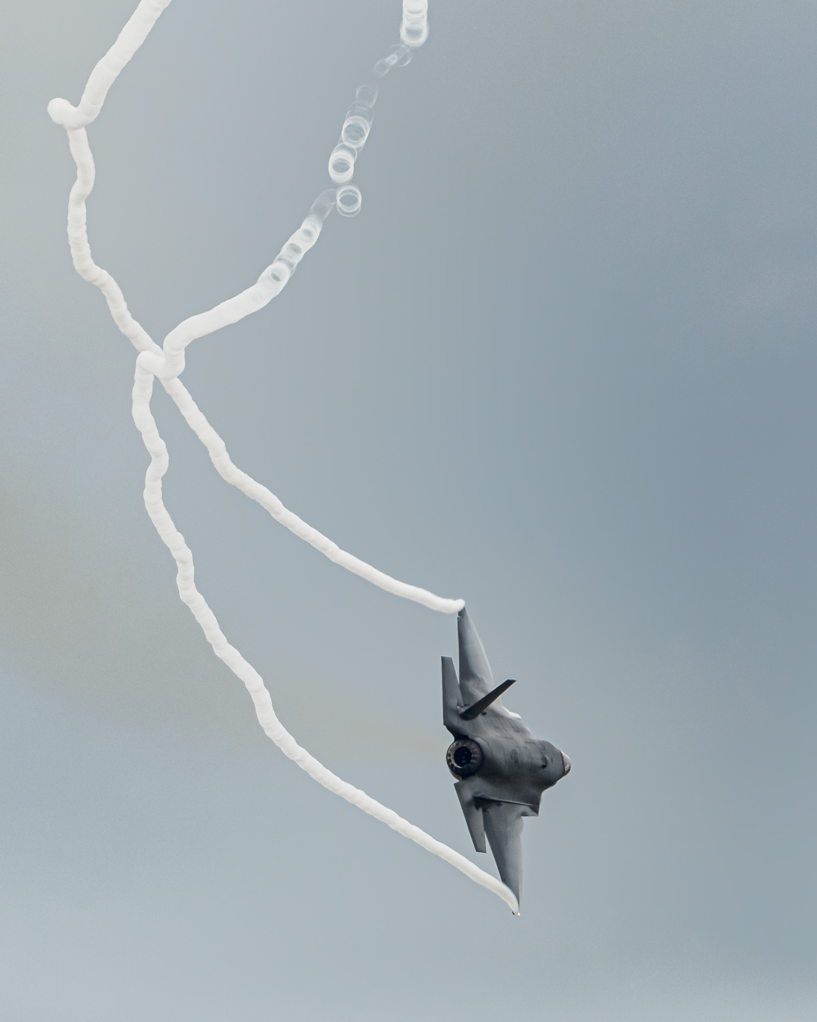 RAF F-35 Lightning-II streaming vapour from its wingtips: the vapour seems to break up into bubbles.