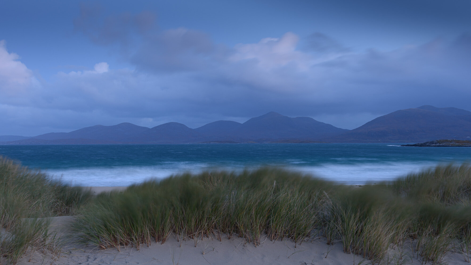 Blue hour before dawn over the grasses on sand dunes over to Taransay