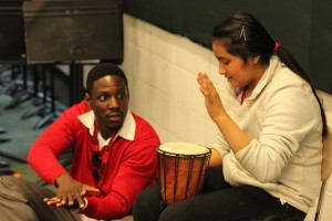 A teacher shows a young student how to play the drum.