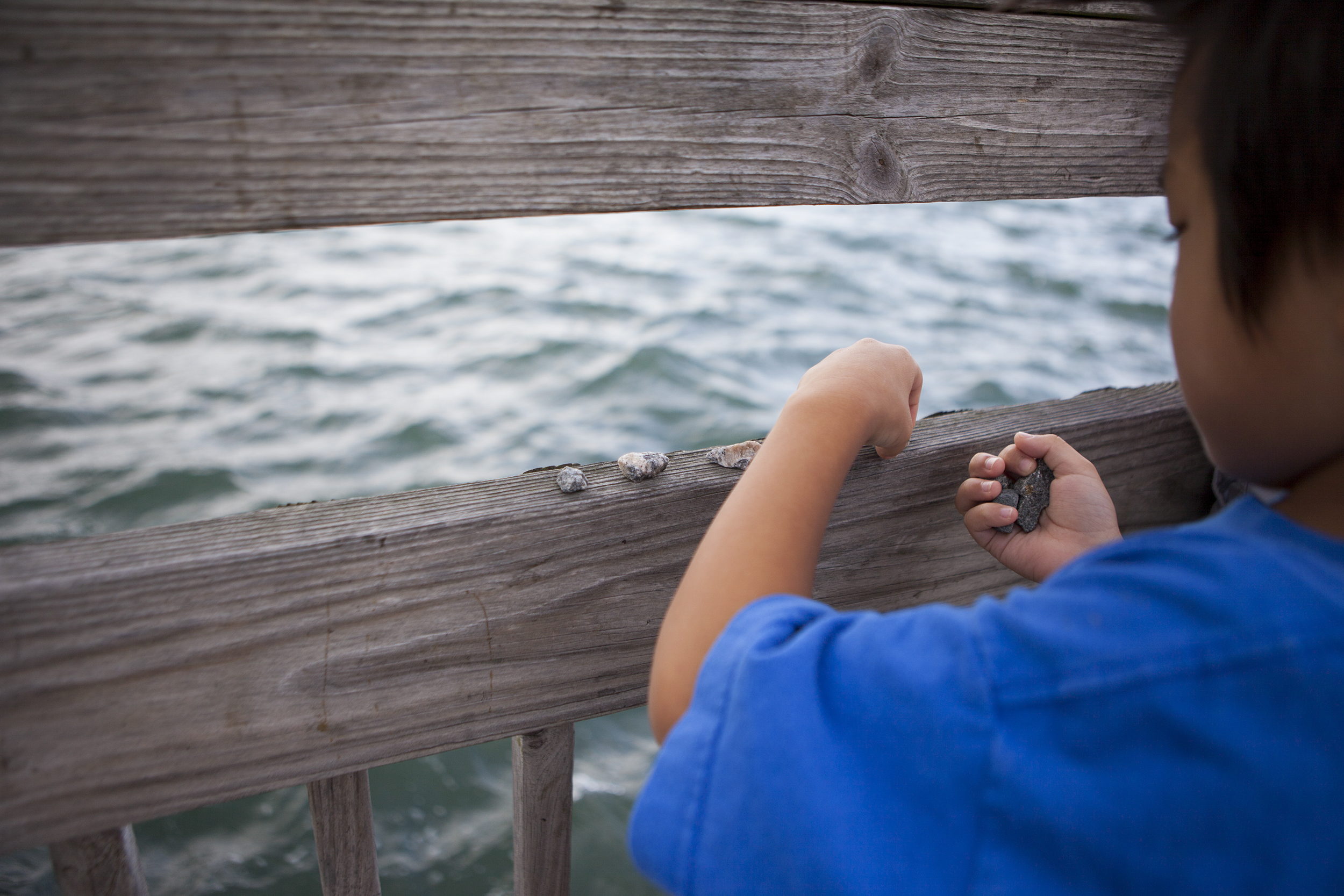 Theodore lines up rocks in a row on the railing of a fishing pier. No fish were caught that day.