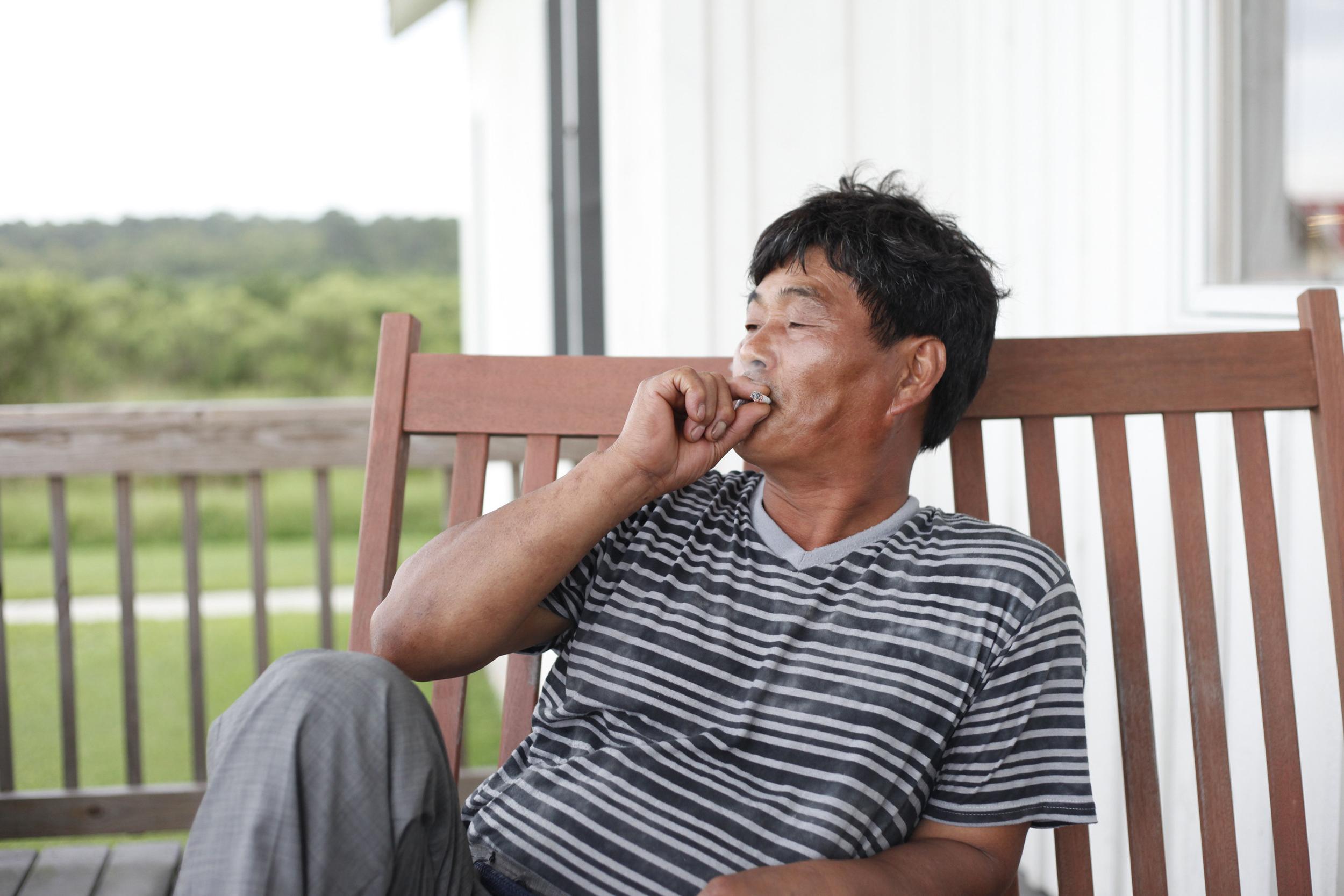 Stanley's father Ki Chang-Sik takes a drag of a cigarette.
