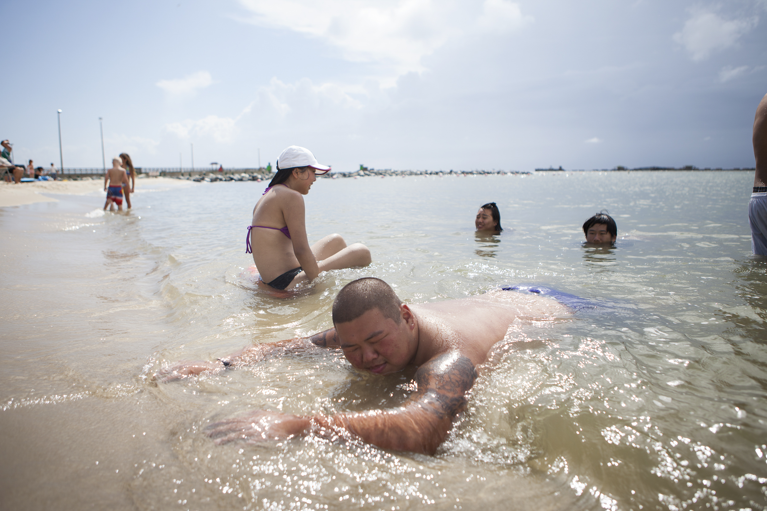 Stanley Ki, 20, basks on the sand.