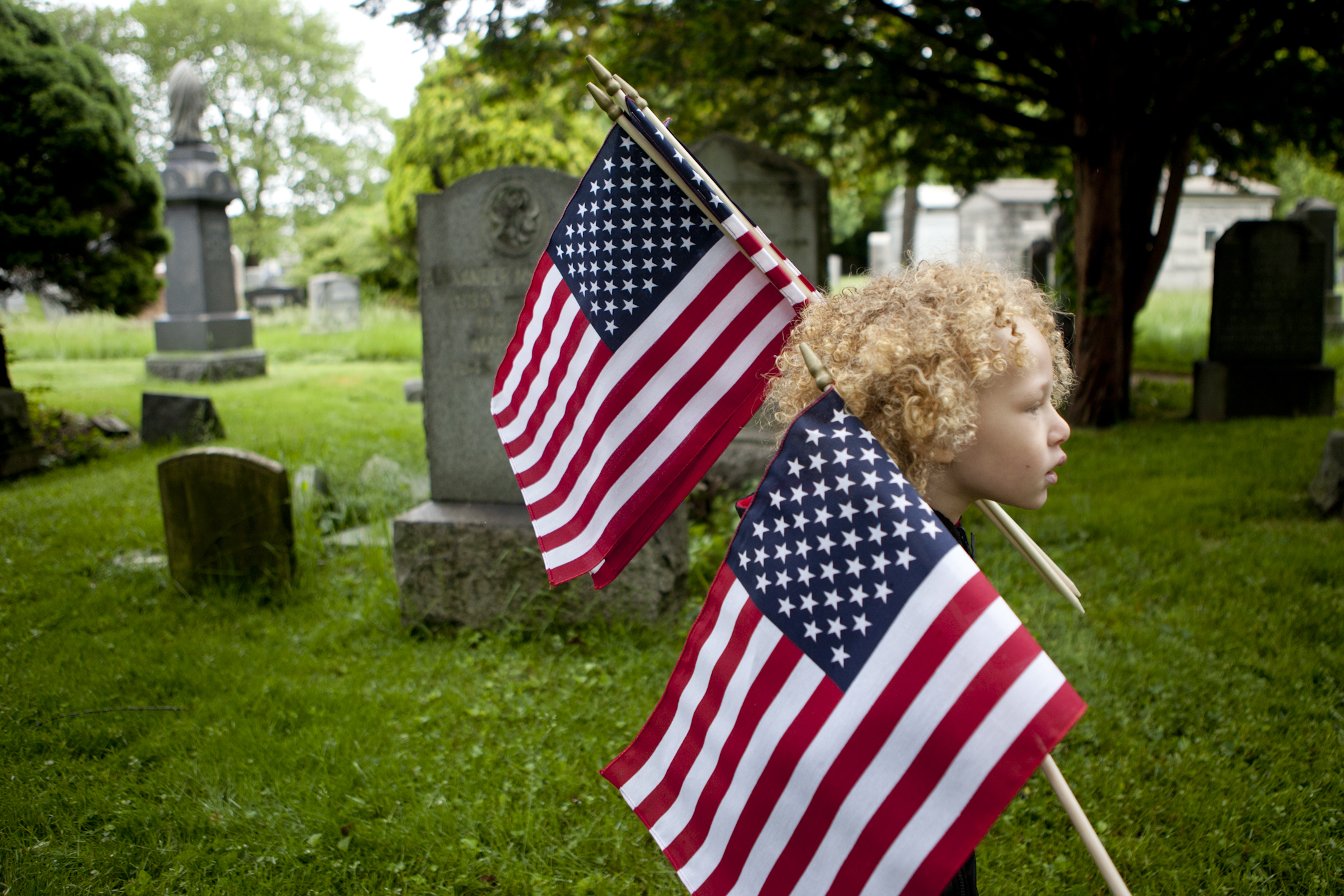 Jahvanni Gifford, 4, carries flags to place at veteran's graves on Memorial Day at Bayview Cemetery in Jersey City. Roughly a dozen service members and thirty children representing various scout troops came together to honor the veterans.