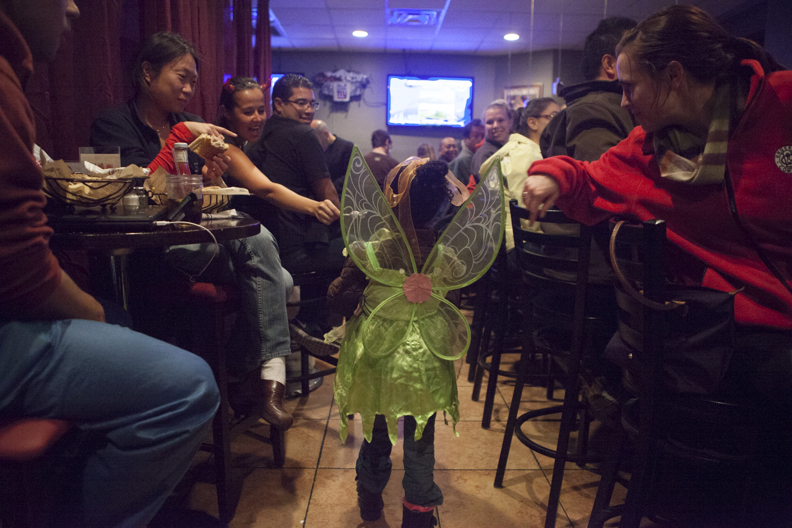 Asha enters a packed bar. Patrons offer her candy.
