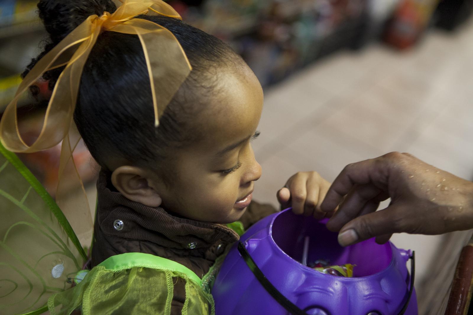 A clerk drops candy into her purple pumpkin head bucket.