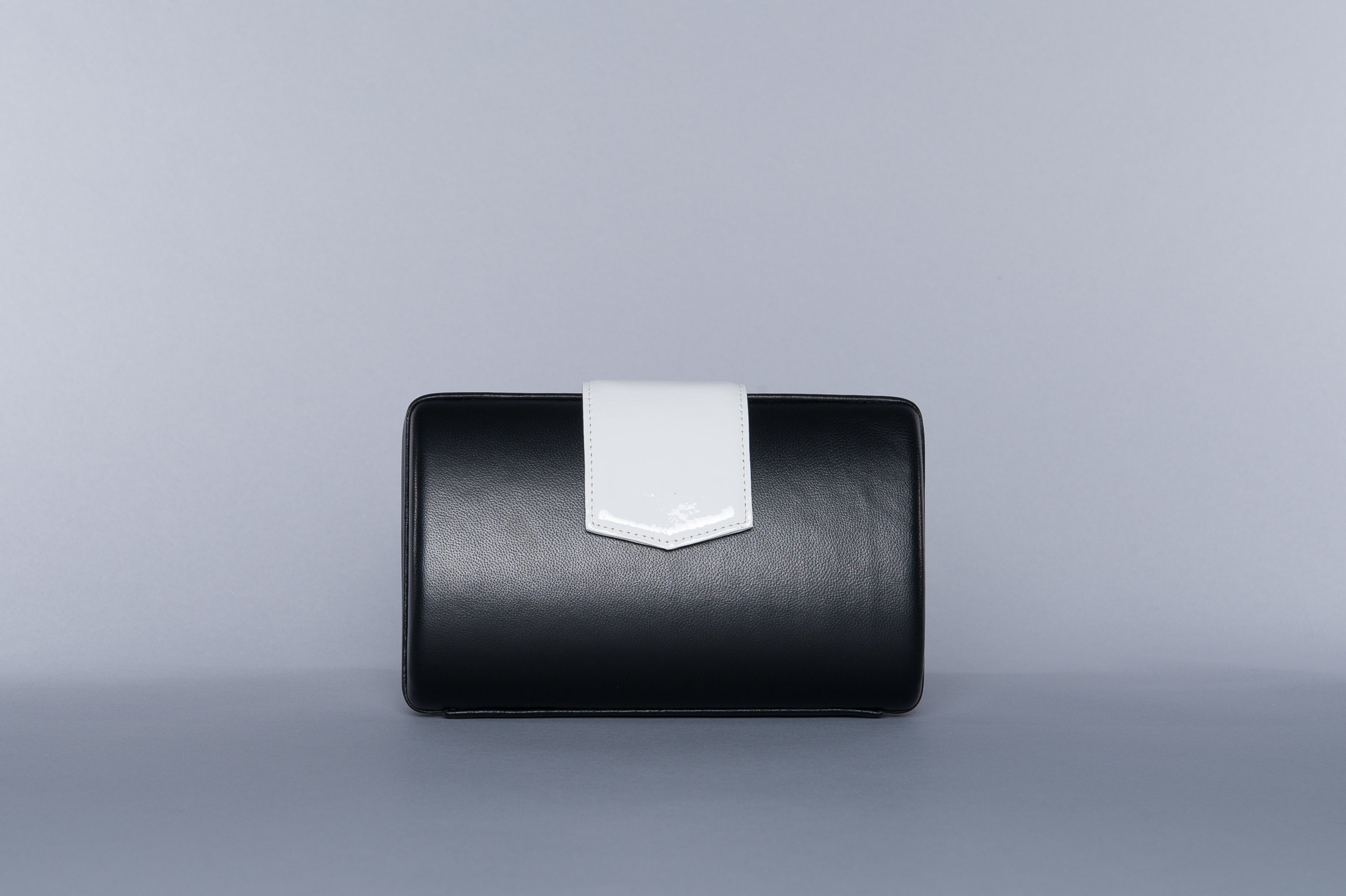 The CLIO - our update on the evening clutch. Its large tab closure accentuates its sleek silhouette -