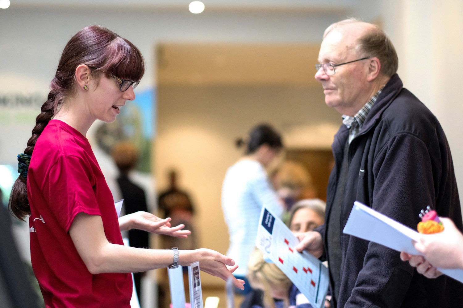 Volunteer explaining mathematical colouring handouts to a visitor at the Dunedin Maths Craft Day 2018