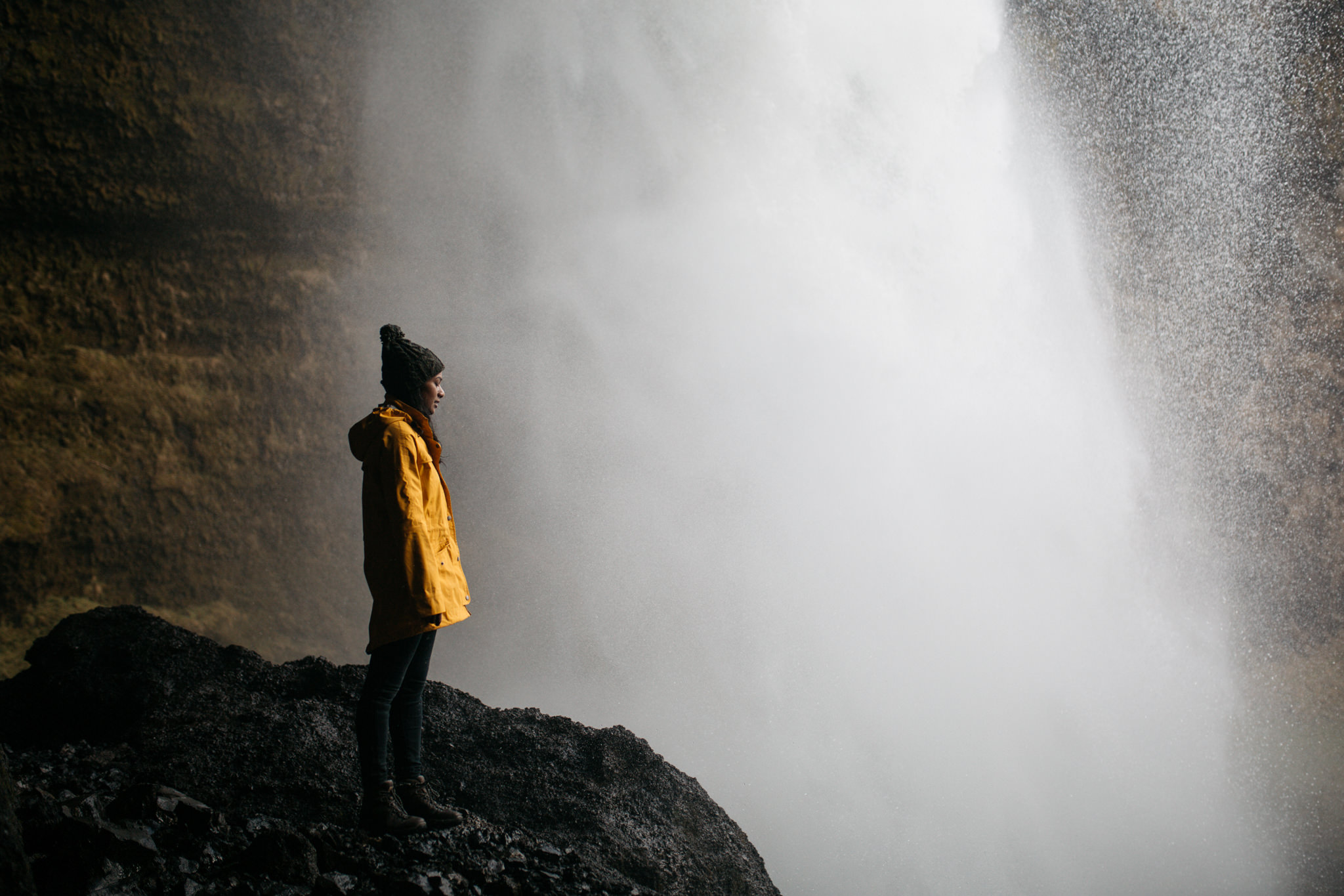 Monita behind hidden waterfall in Iceland with yellow jacket