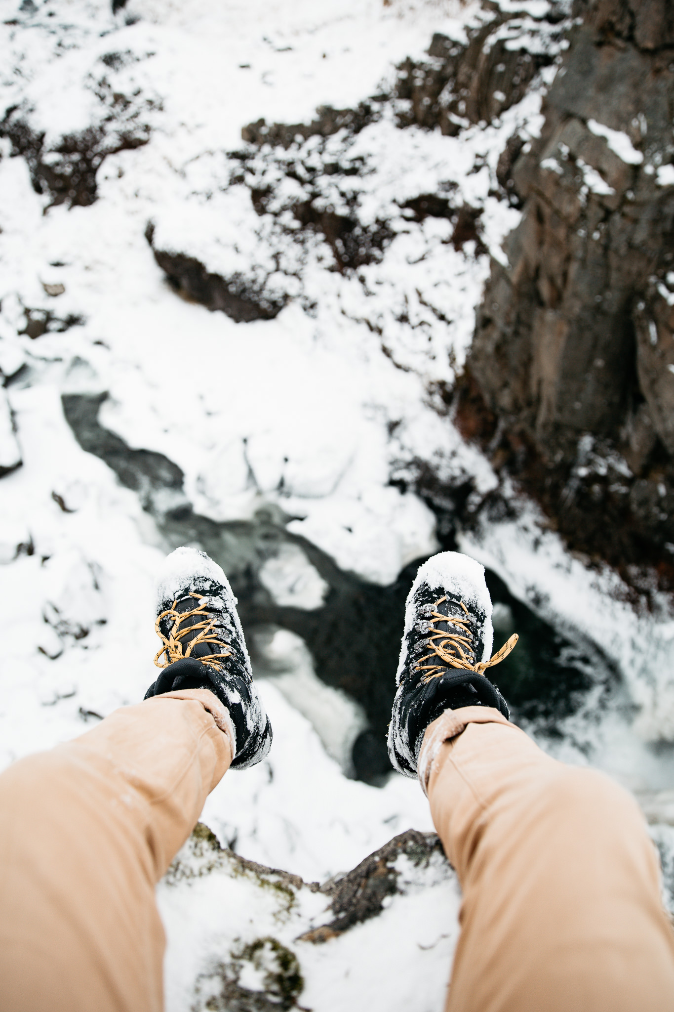 Feet with hiking boots over private waterfall in Iceland during winter