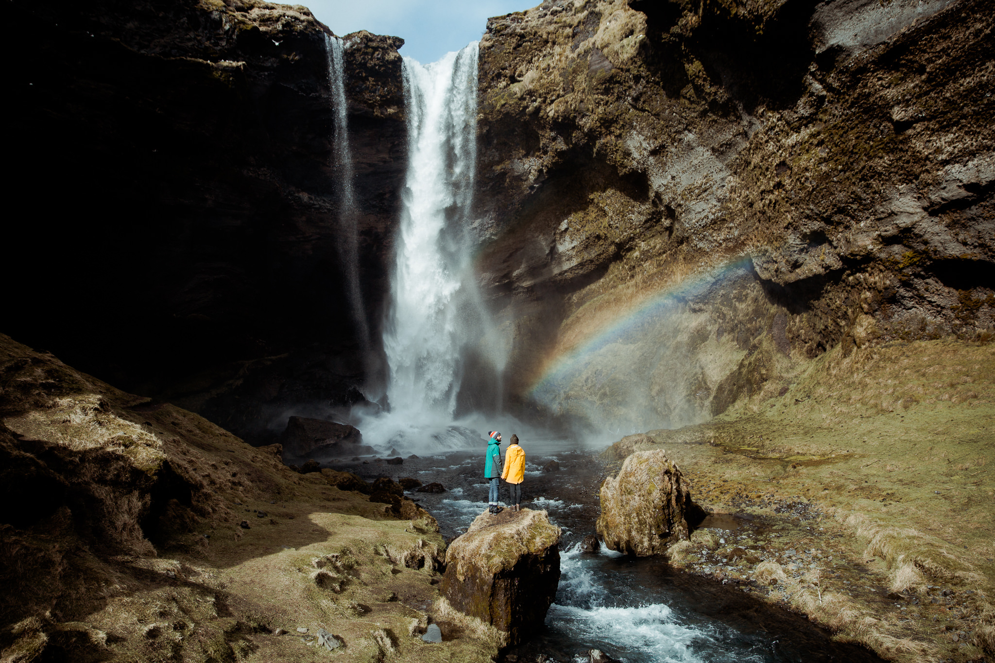 Monita and I in front of hidden waterfall in iceland with a rainbow