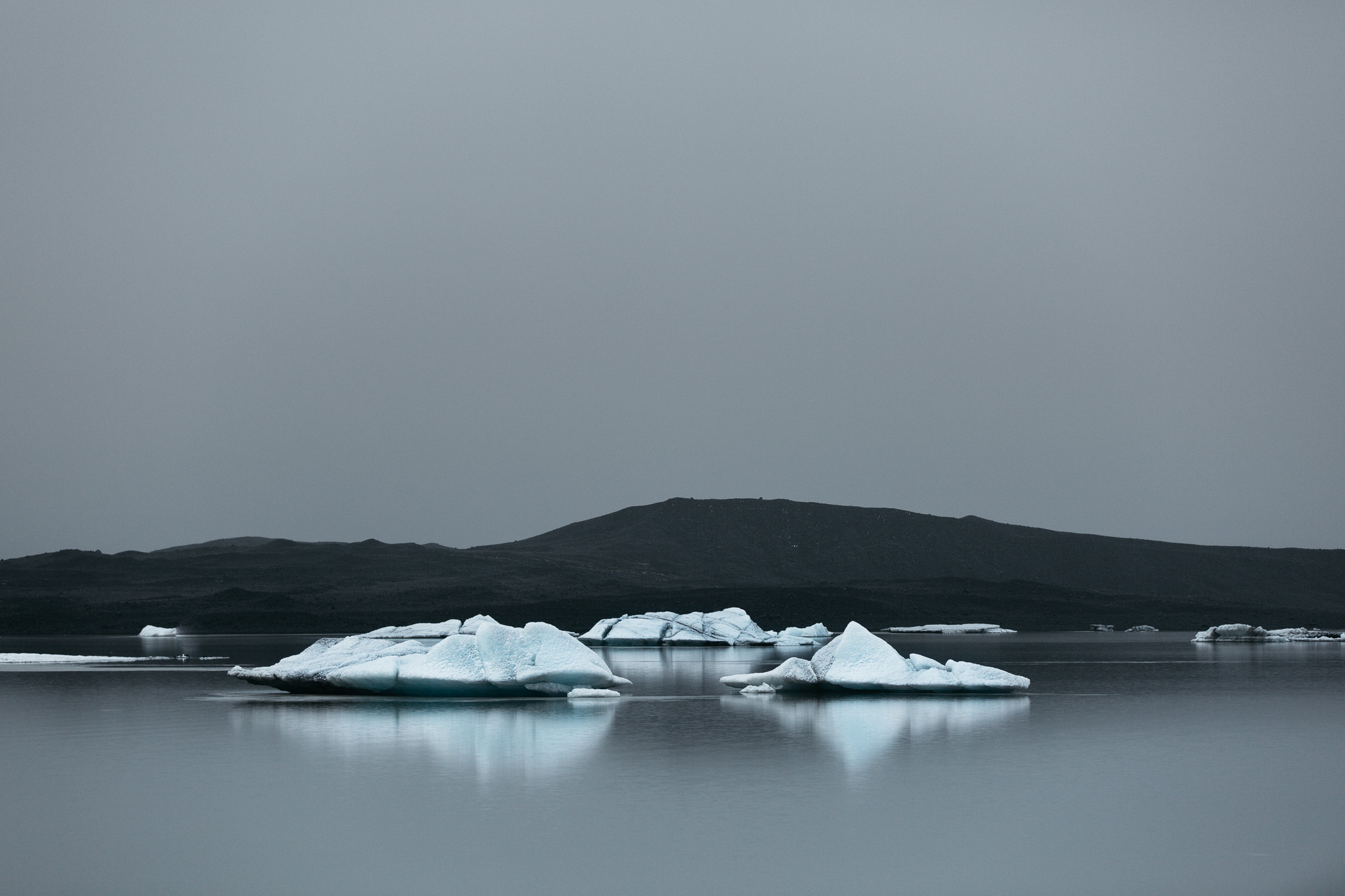 Three large floating icebergs at Skaftafellsjökull lagoon during winter