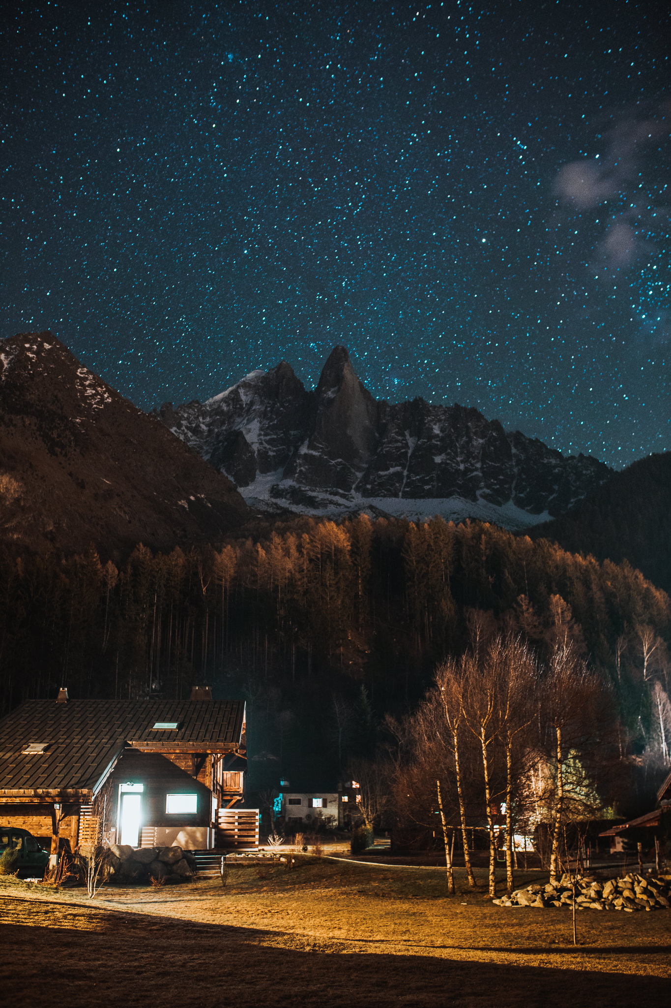 wooden house in foreground at night with mountain and stars in the background