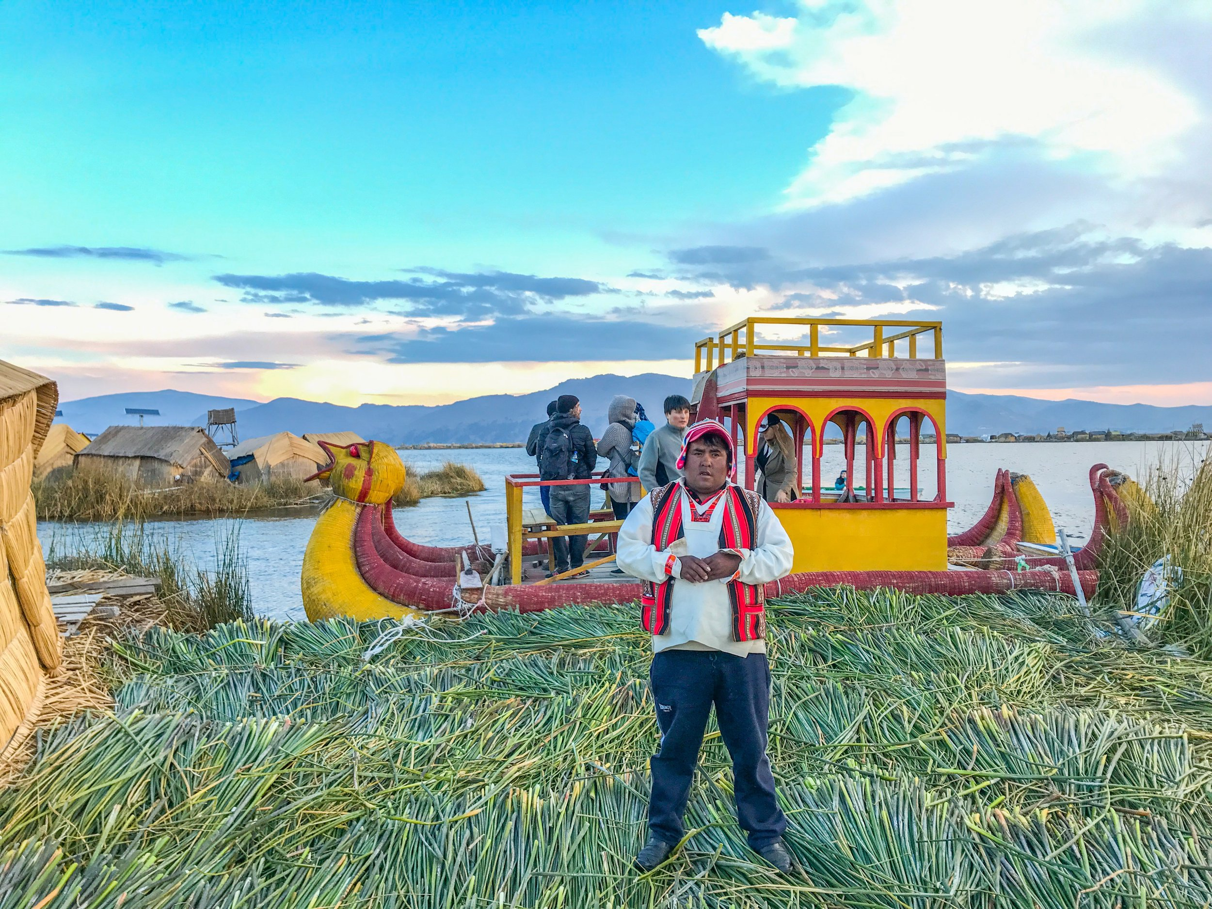 The Uros island chief posing in front of the Mercedes Benz boat in Puno