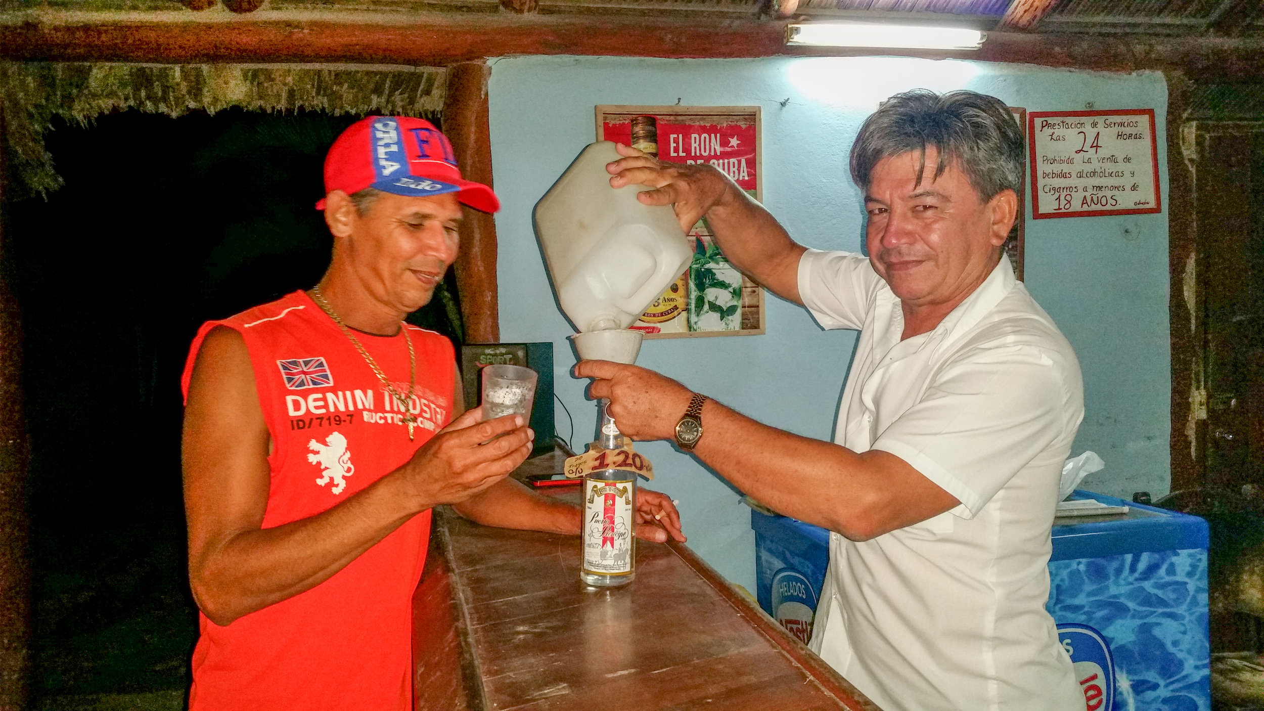 A bartender in Santa Lucia, Camaguey, pouring beer from recycled containers