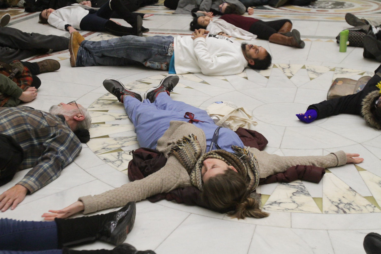 """Katrina Ciraldo-Maryniuk, a family medicine intern at Boston Medical Center, lies on the ground in the Massachusetts State House in protest of Governor Baker's recent budget cuts to substance abuse prevention programs. """"My best friend died from an overdose in my first year of med school,"""" she said."""