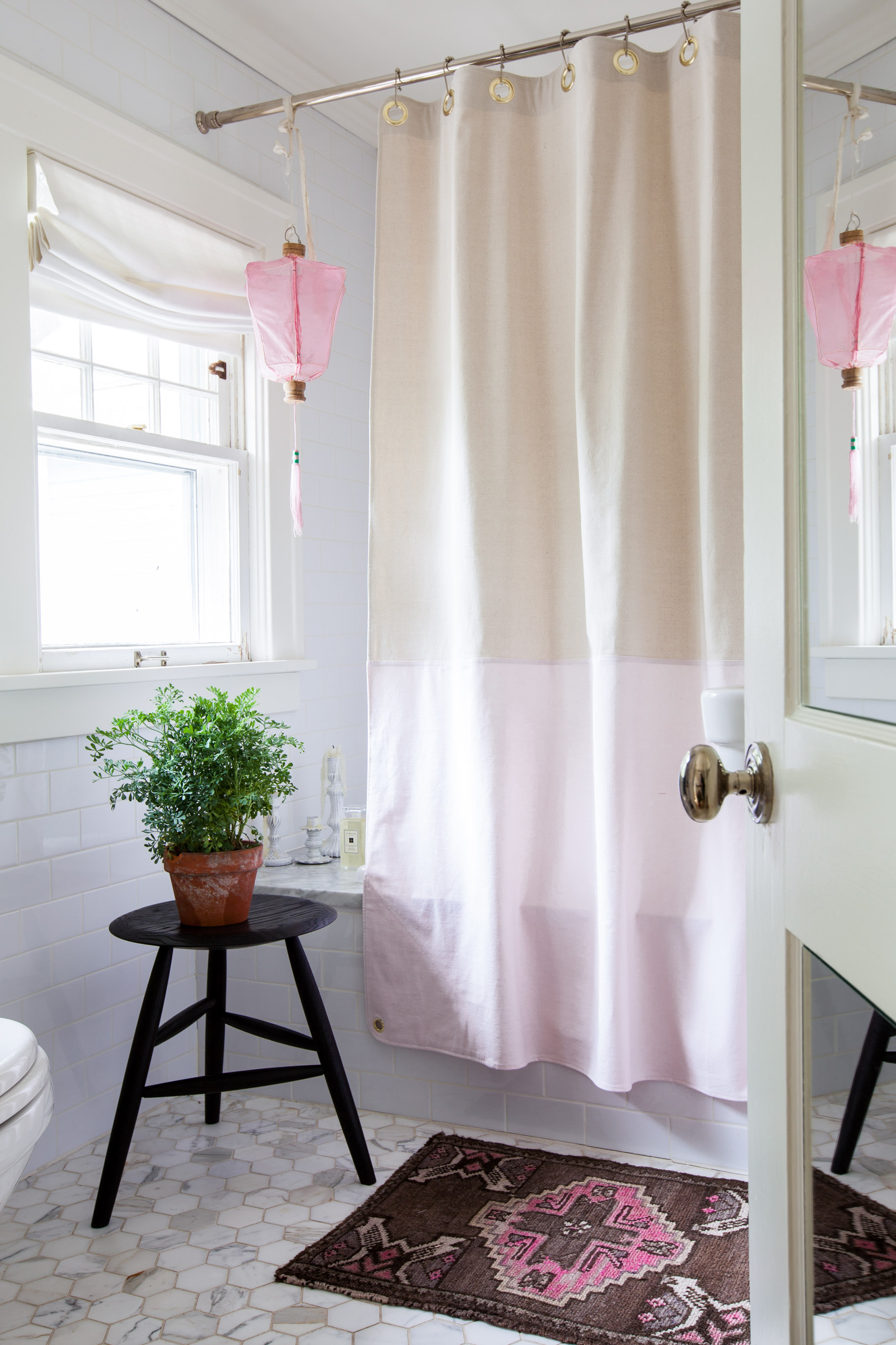 """Heated floors and tons of natural light make Michelle's master bath one of her favorite rooms in her house. Above the bath hangs a lantern that she purchased in college and has since moved with her to eleven apartments and one home. """"I can't seem to part with it. It's such a cheerful piece!"""" says Adams.Photo by  Marta Xochilt Perez"""