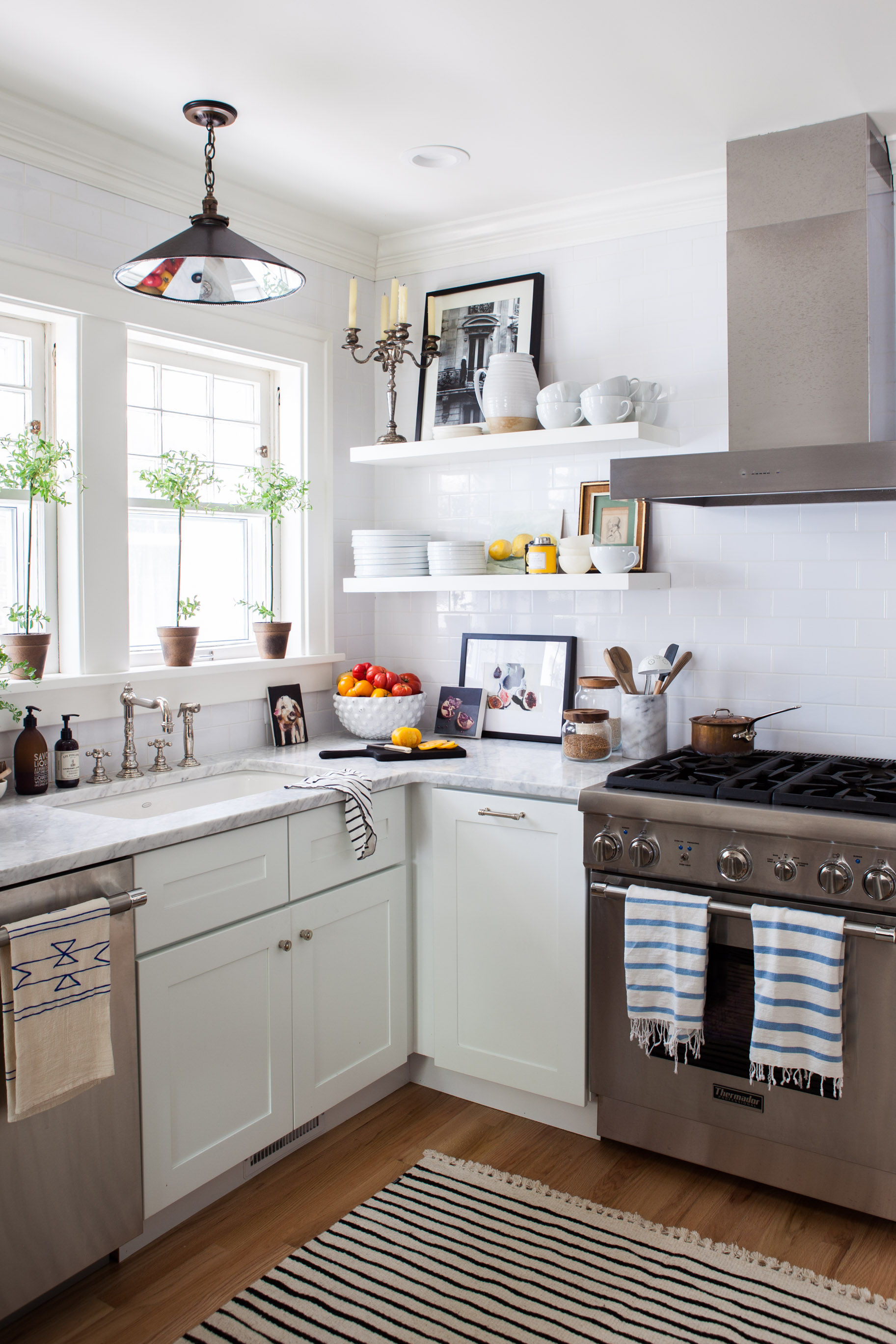"""After nearly a decade of apartment dwelling in New York, Michelle was thrilled to design her first """"real"""" kitchen and learn how to cook.  Figs by Giulia Bianchi  and  Untitled by Pavel Feinstein  add a splash of color to the whitewashed space.Photo by  Marta Xochilt Perez"""