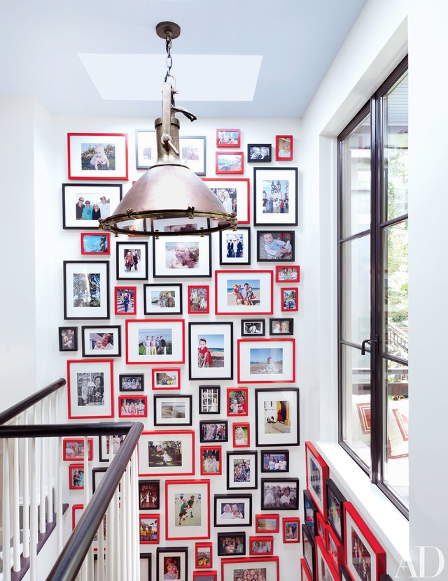 Family photographs are hung salon style in the rear stairwell of a  Brooklyn brownstone decorated by Nick Olsen .