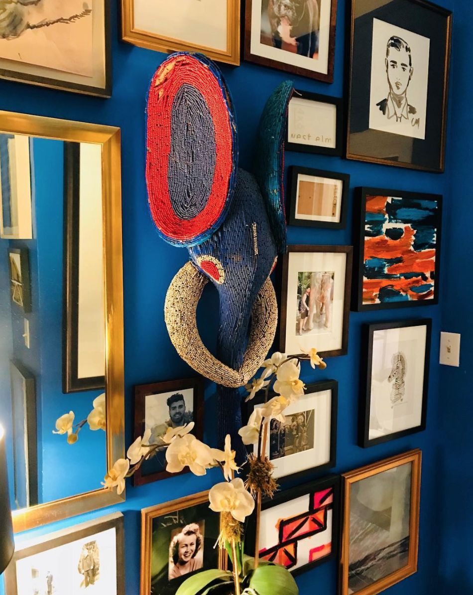 A lively gallery wall in Anthony's apartment, featuring a mix of his artwork, family photos and vintage finds.