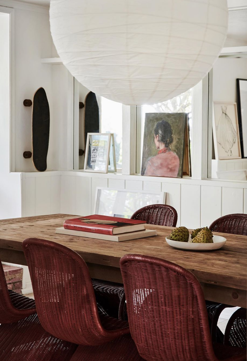 Leanne Ford  leans art in a dining room surrounded by a mirrored ledge.