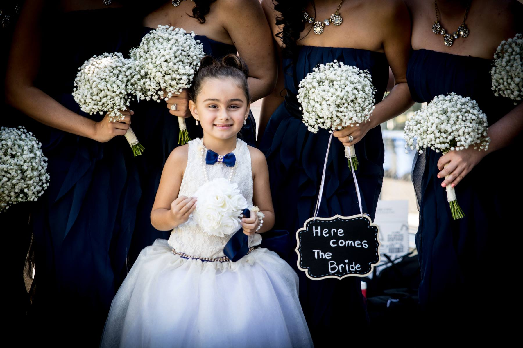 Flower girl with sign that says Here Comes The Bride