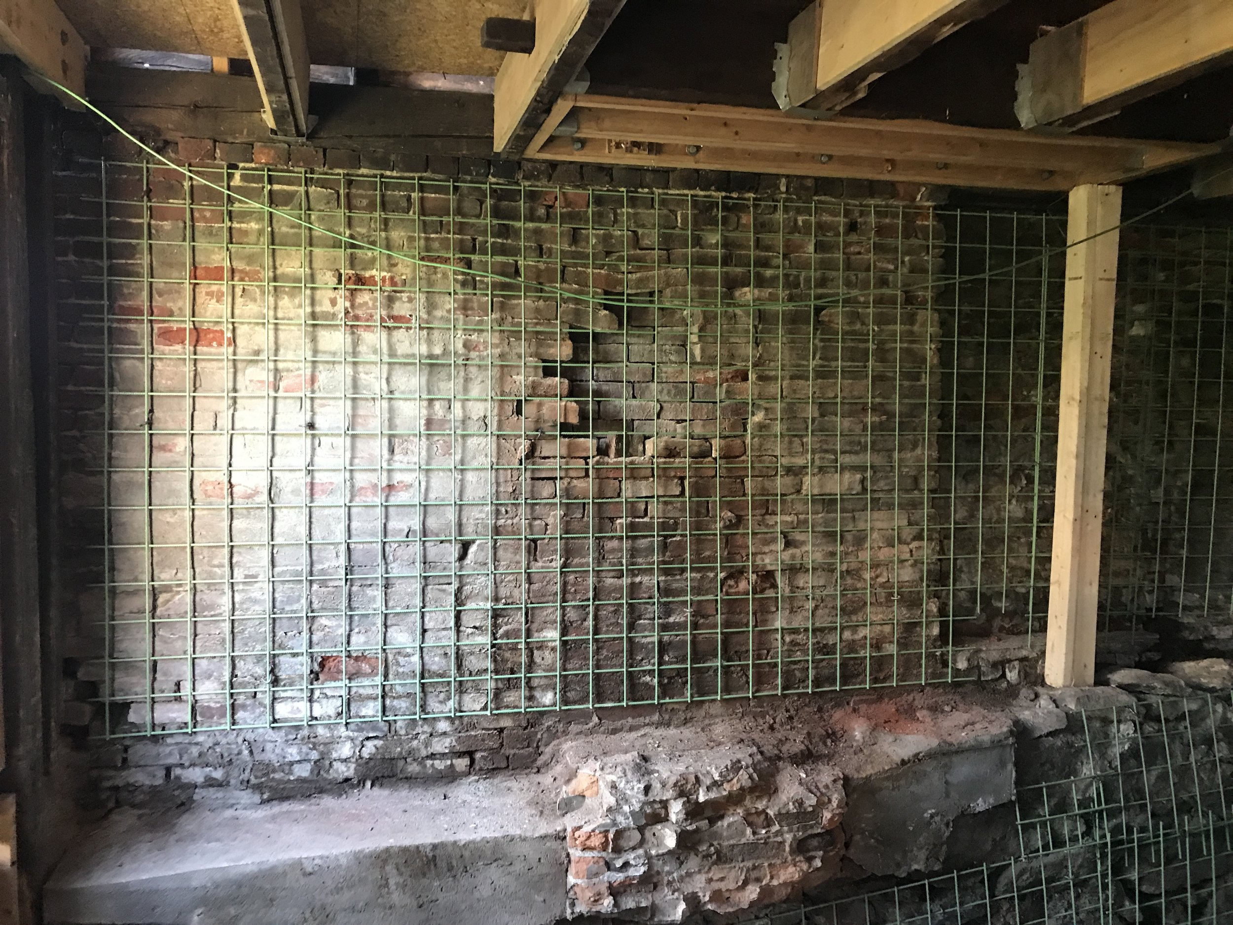 We decided to use reinforced rebar sheet and 3-4 inches of 7500 PSI shotcrete in order to rebuild and stabilize the foundation.