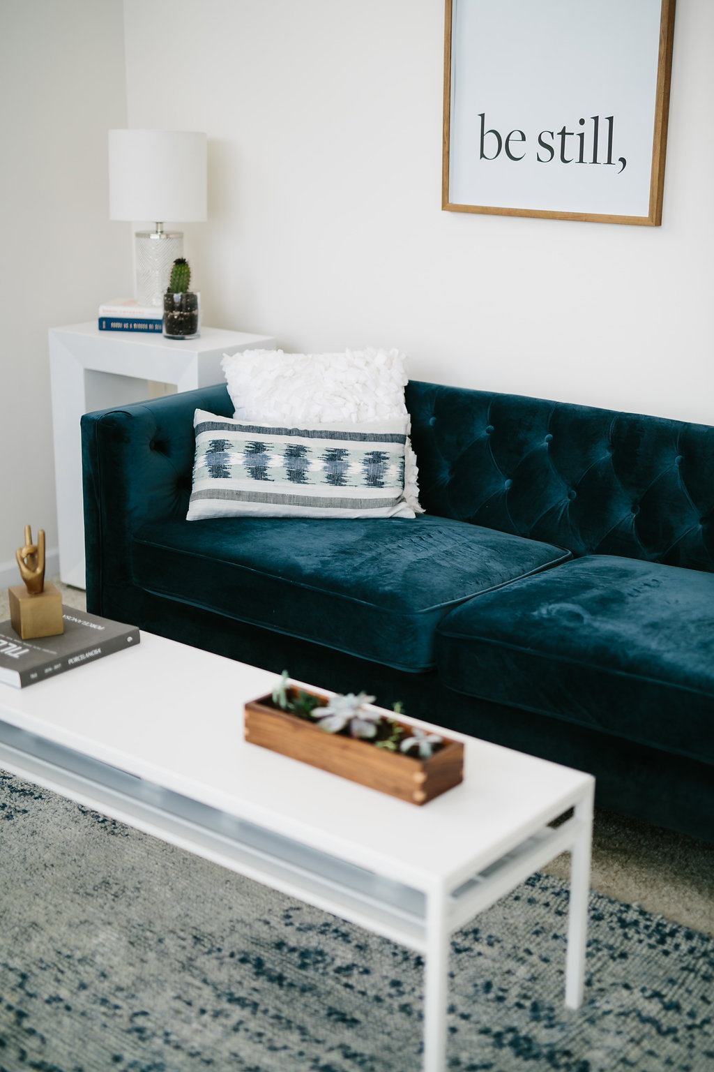 A blue tufted sofa with home decor on a white coffee table.