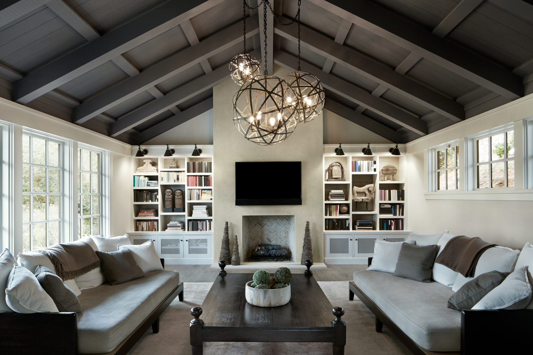 A living room design with two sofas, a coffee table and built-in bookcases flanking the fireplace. An open ceiling and oversized chandeliers showcase the natural beauty of this home.