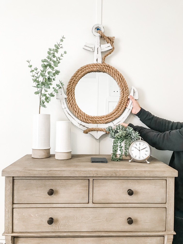 A distressed wood dresser with interior decor, faux plants and a distressed wood mirror.
