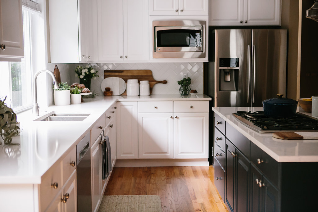 Navy blue kitchen cabinets in this Kirkland, Washington island are complimented by white kitchen cabinets and finished with Pental Quartz white countertops.
