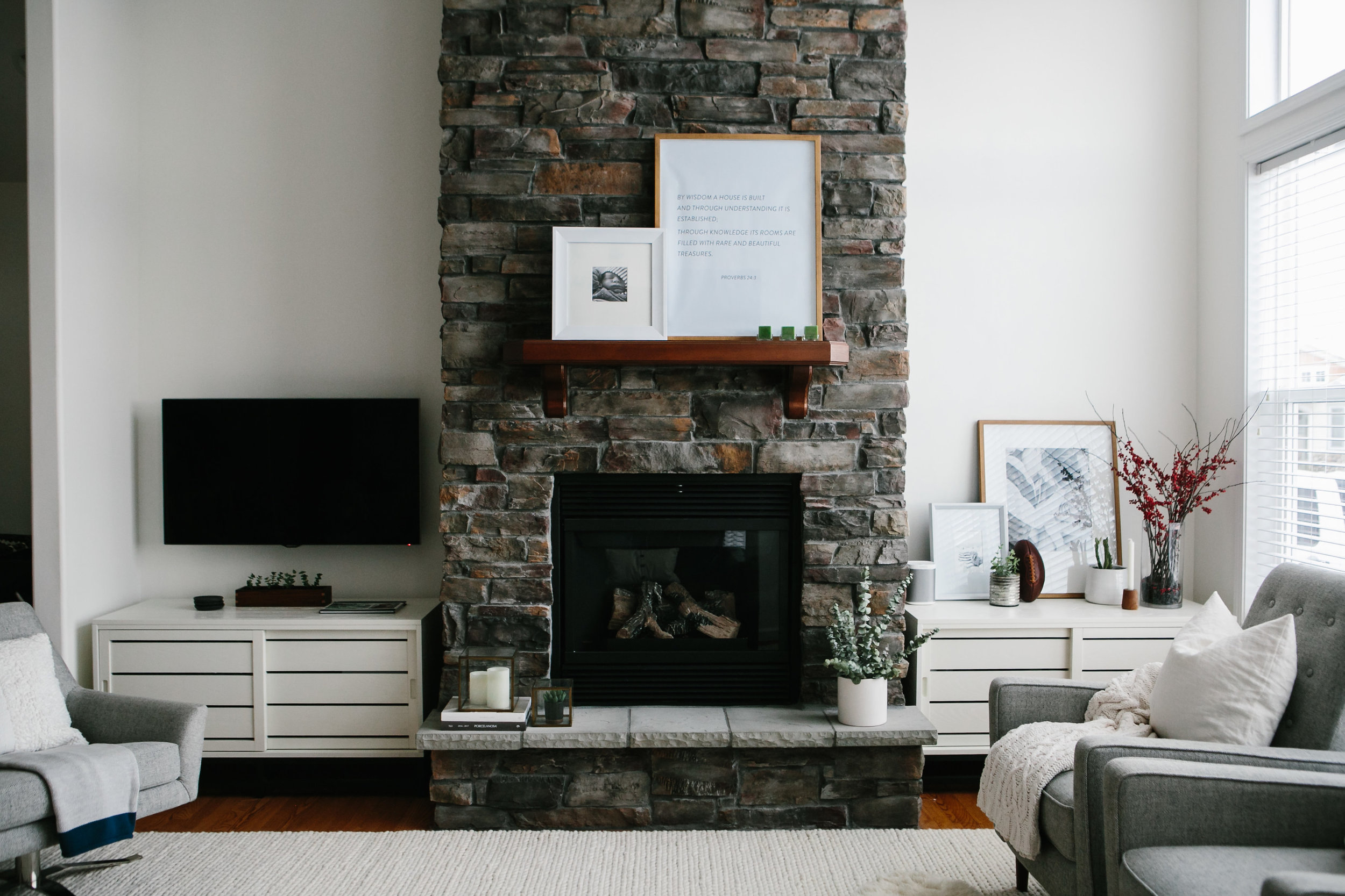 Natural stone grand fireplace with white Crate and Barrel base cabinets in a modern coastal home.