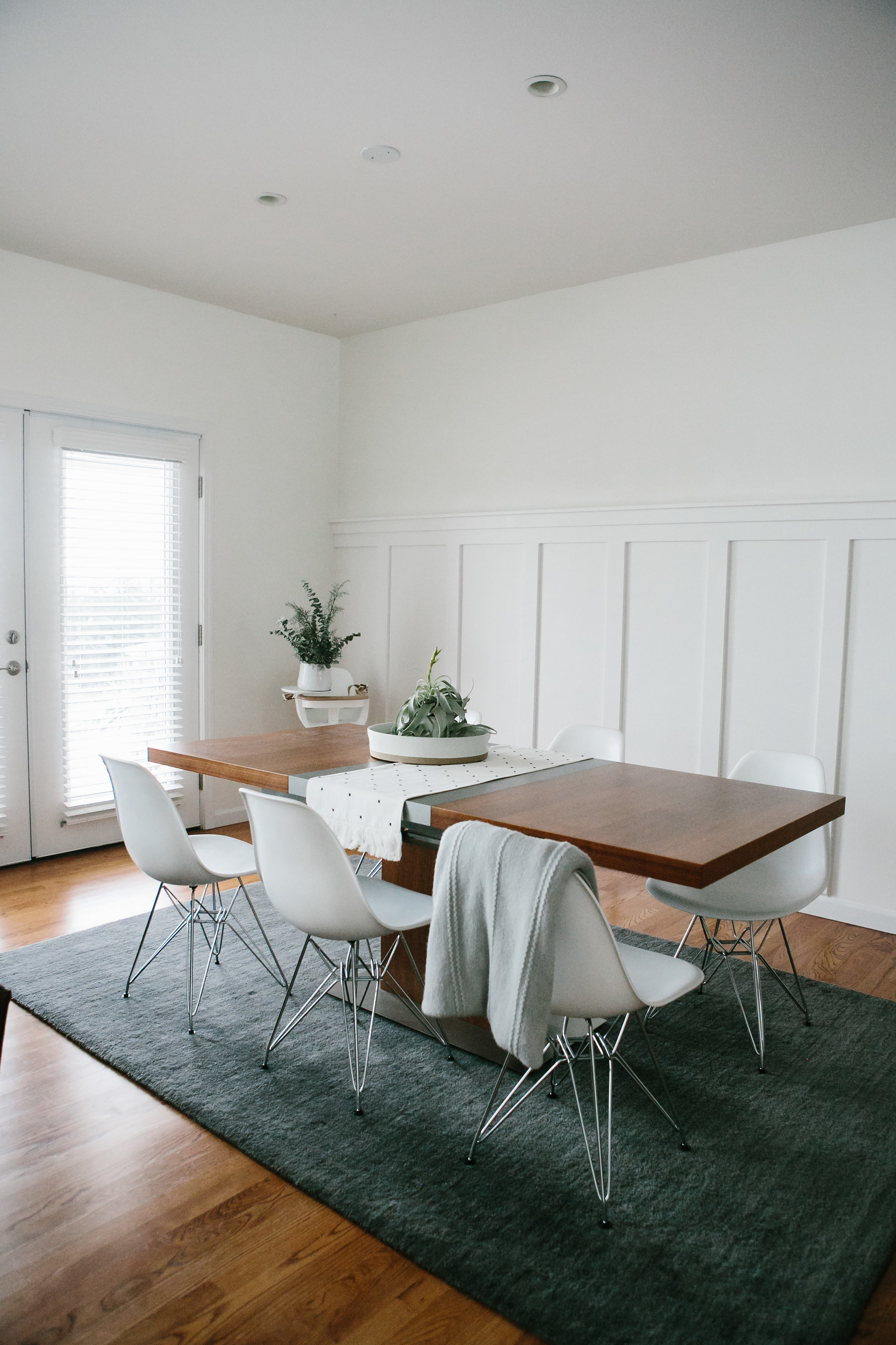 A sleek modern dining table with mid century modern dining chairs and a gray rug.
