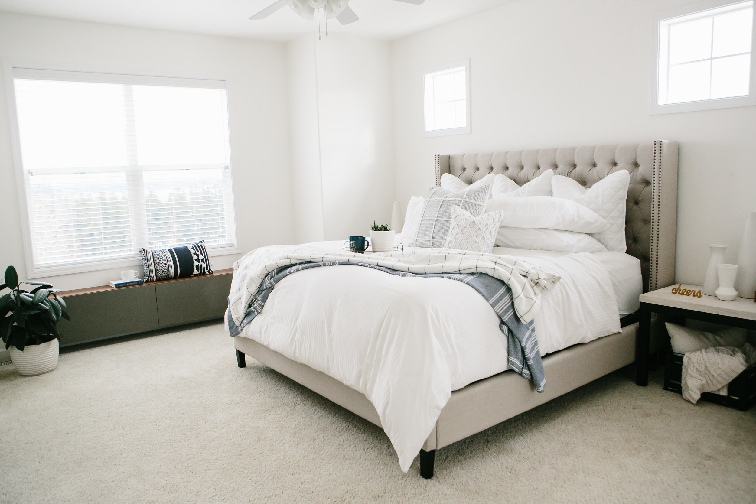 A clean transitional master bedroom with an upholstered headboard.
