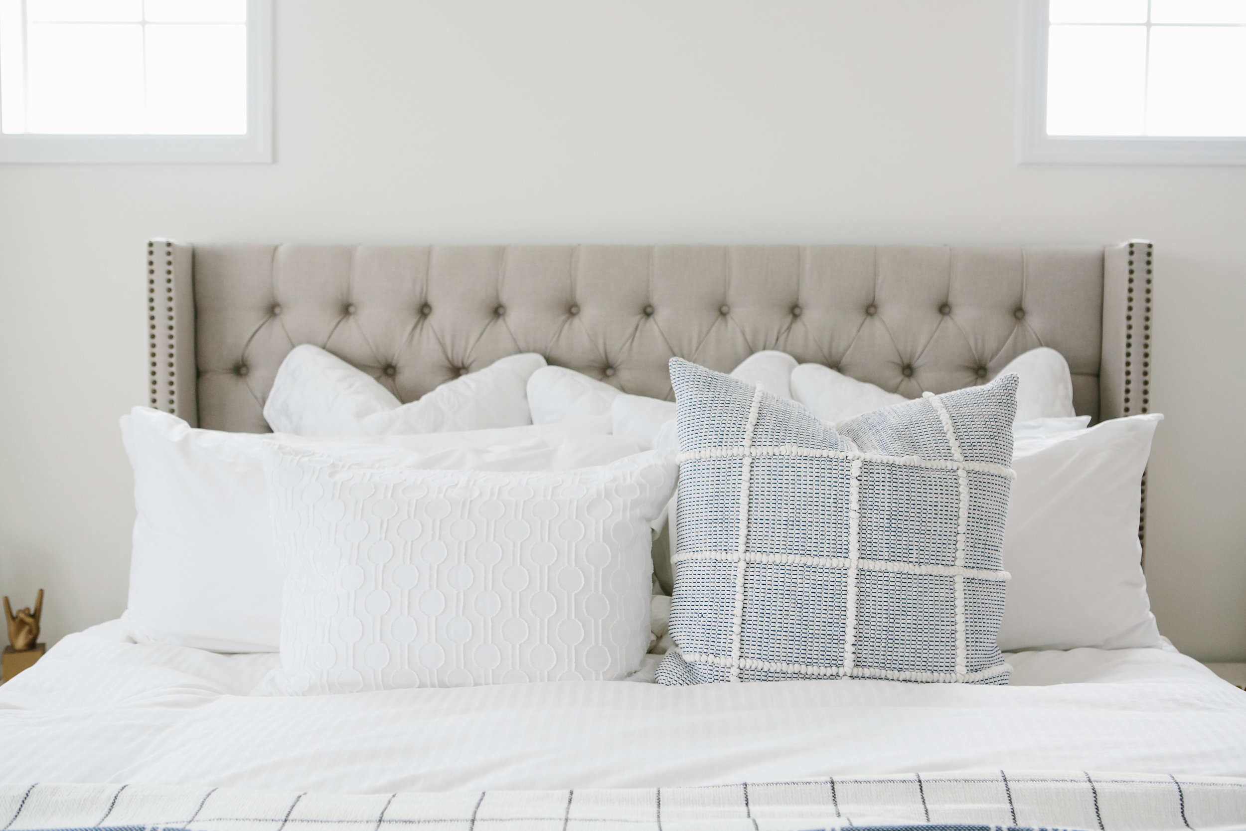 Master bed pillows in white and blue.