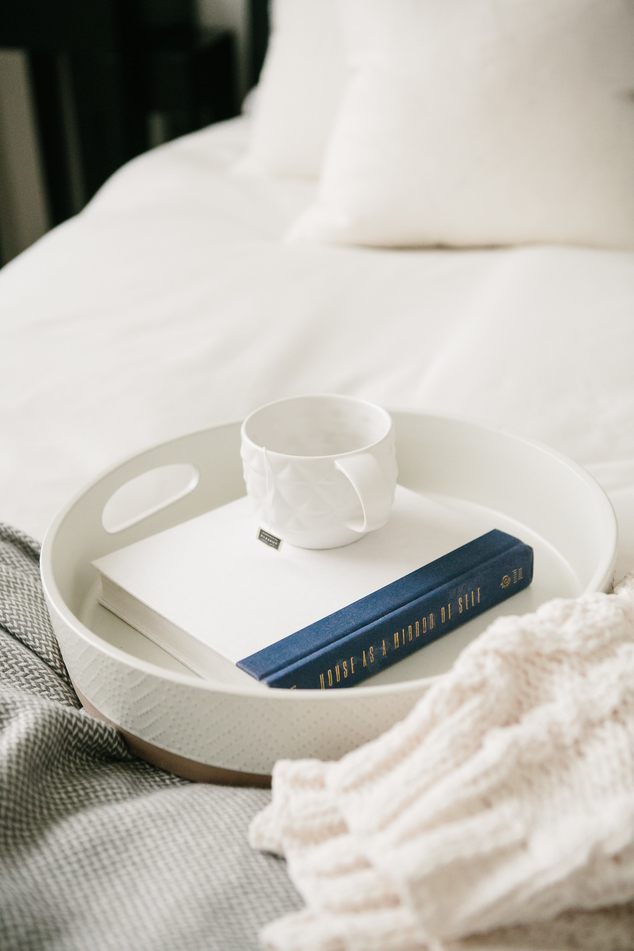 A tray, book and mug on a guest bedroom designed by an interior designer.
