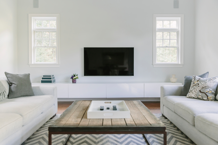 Wood coffee table with white media console and tray.