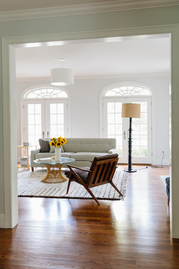 Living room with bright natural light and a glass coffee table.