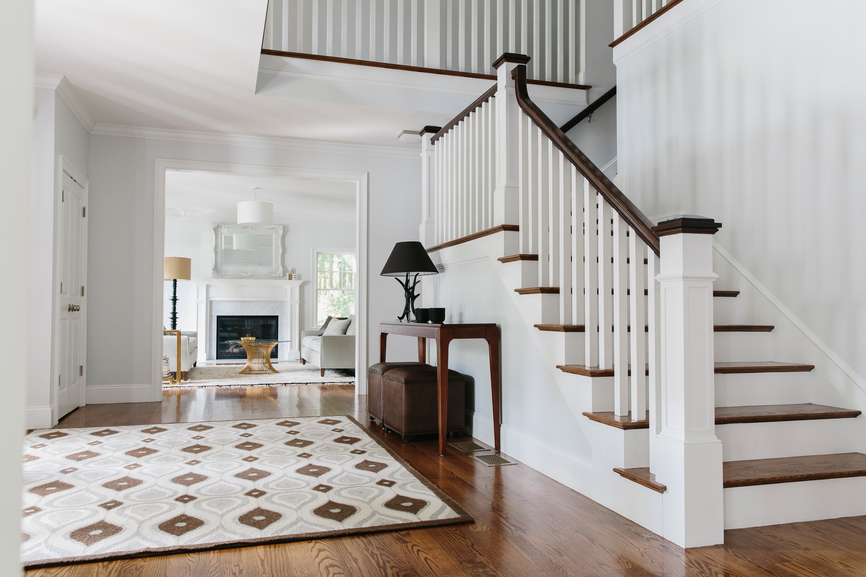 Wood banister and stairs with hardwood floors in entryway.