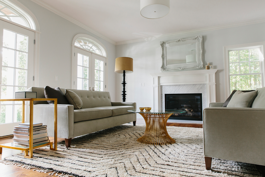 Button tuffted sofa with modern lines and a marble fireplace.