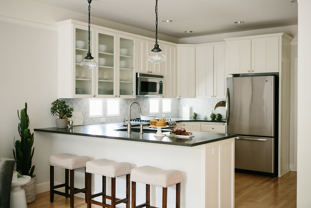 Transitional modern kitchen with white cabinets, stainless steel appliances, hardwood floors and dark grey caesarstone countertops. Upholstered barstools and restoration hardware pendants highlight this Kirkland, Washington home.