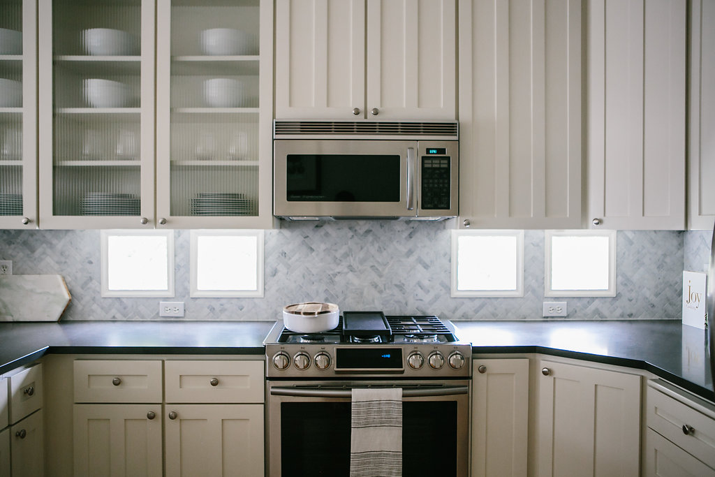 Marble herringbone patterned backsplash and an organized kitchen shelving with white cabinets.
