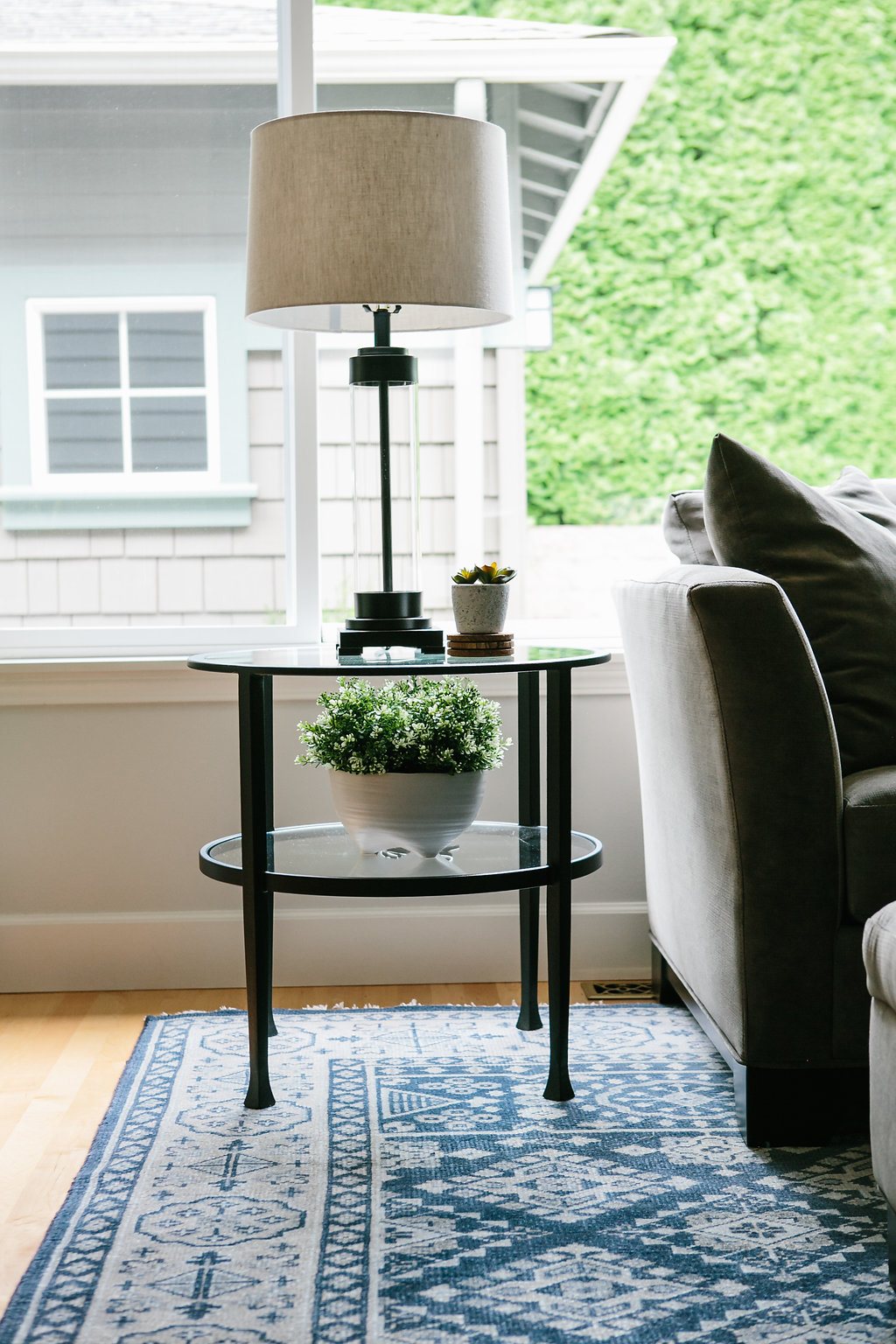 Endtable with lamp on navy blue rug.