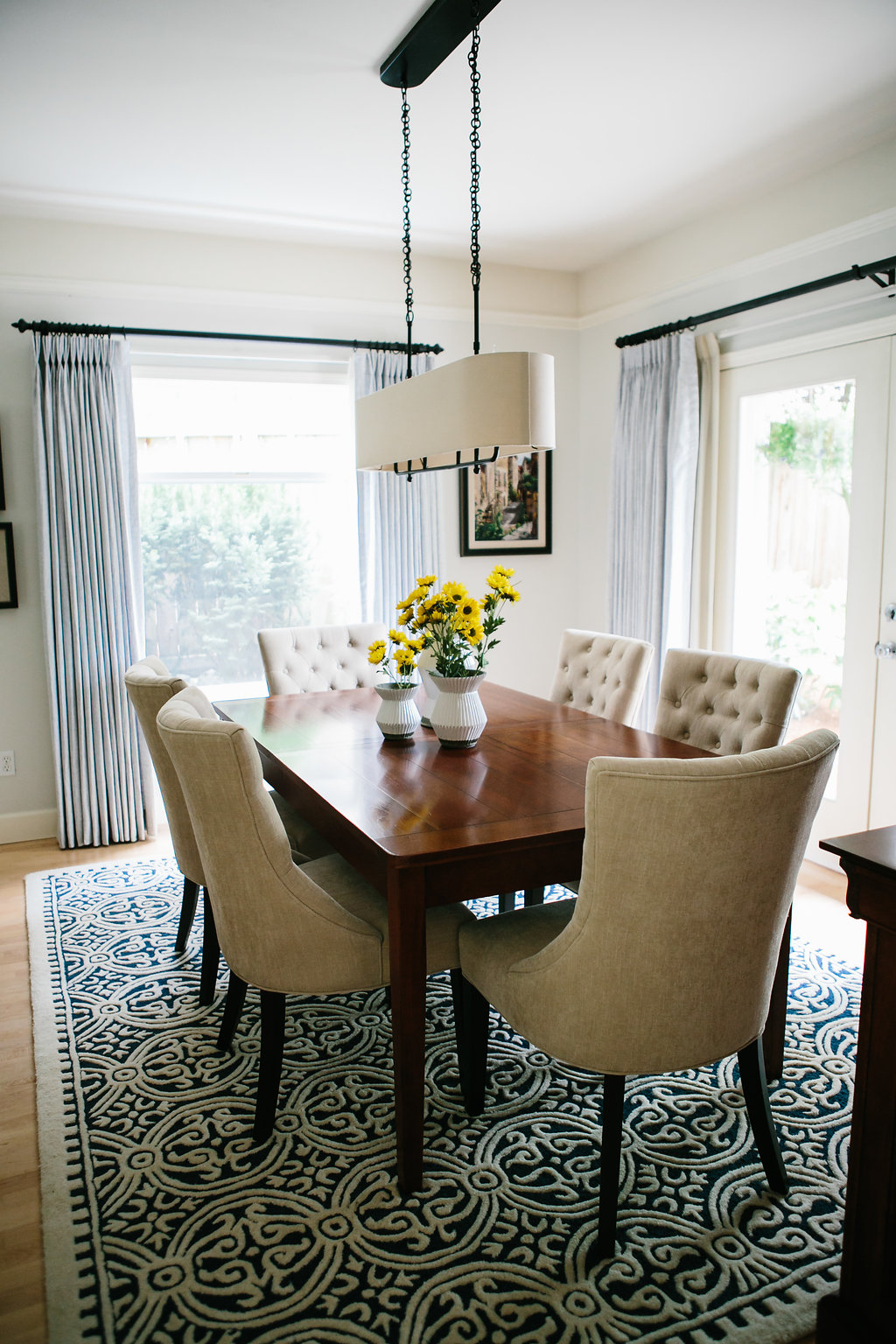 Dining table with chandelier and upholstered dining chairs.