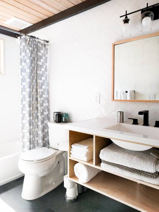 Herringbone subway tiles, slate floors and custom wood vanity make this vacation rental design stunning.