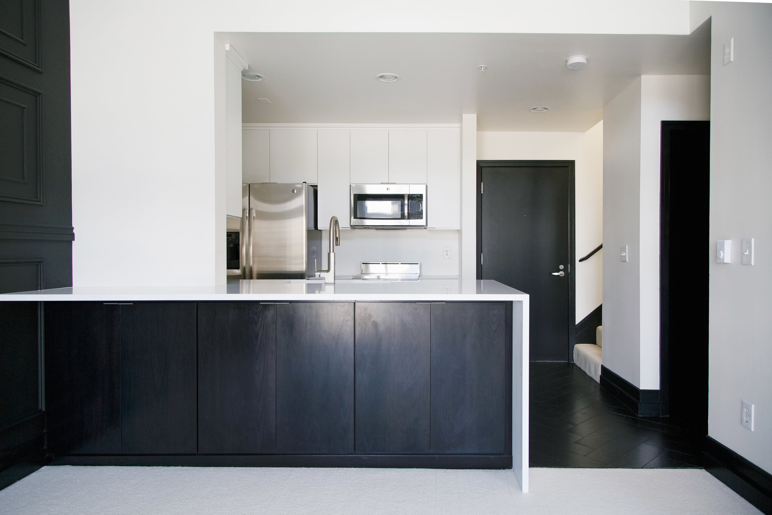 Modern black and white kitchen with pental quartz waterfall countertop and stainless steel appliances. Black herrinbone floors and black wainscot moulding highlight this exception condominium in Seattle, Washington.